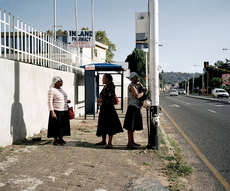 Photographed in South Africa, a group of women stand in the shade, sheltering from the intense heat