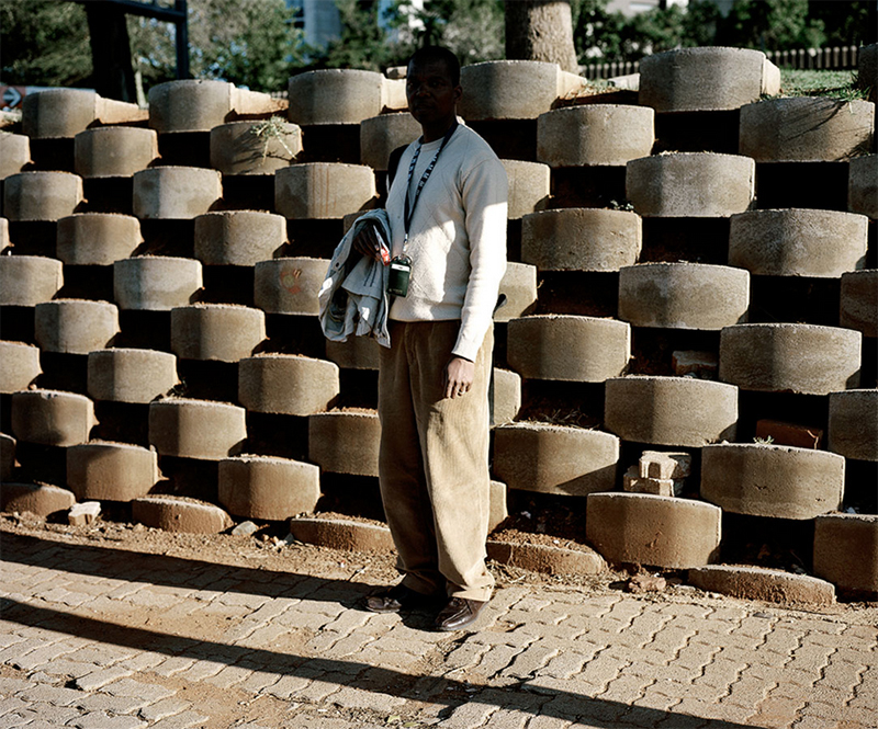 Photographed in South Africa, a man stands in the shade, sheltering from the intense heat