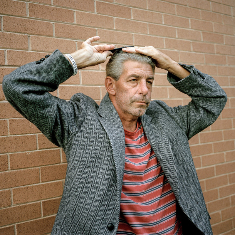 An older man, standing by a wall, combing his hair