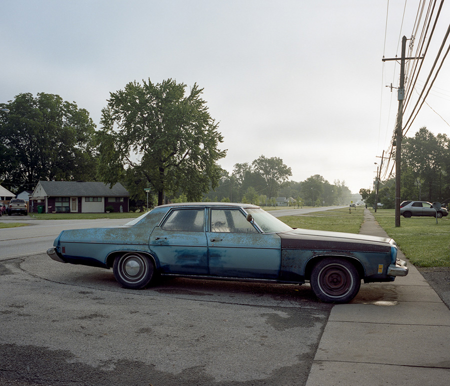 An old blue sedan car, which is parked