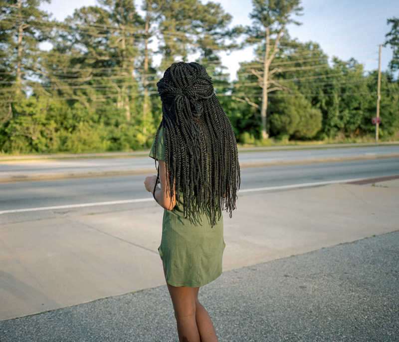 A girl with long braids and a green dress, with her back to the camera,
