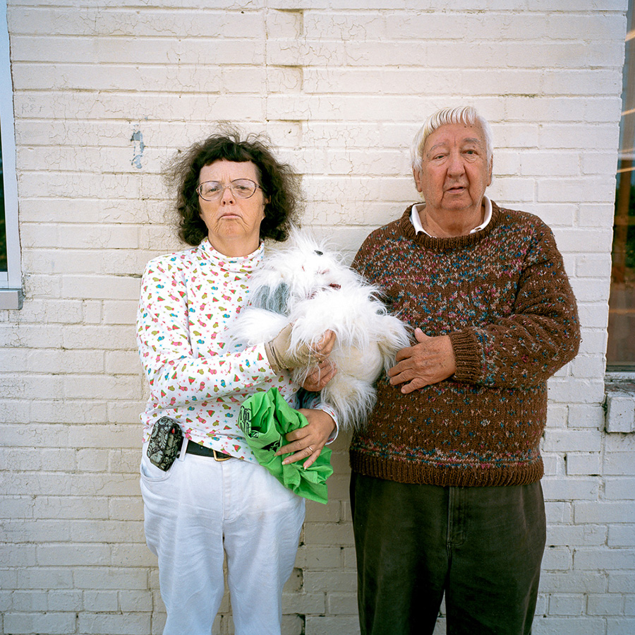 An older couple standing by a white wall, holding a small fluffy white dog