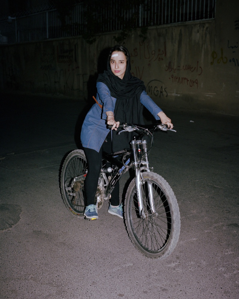 young woman sitting on a bicycle