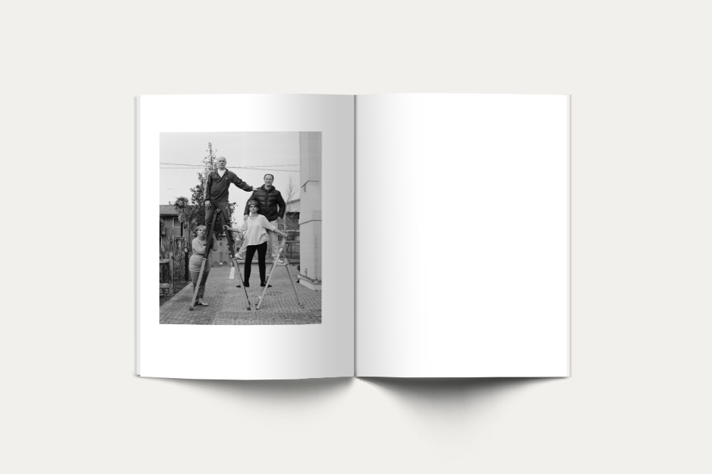 An open book with a black and white photograph of three balancing men on the left page.