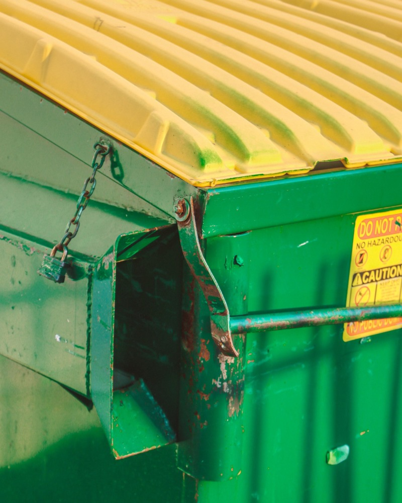 A bright, bold green and yellow dumpster