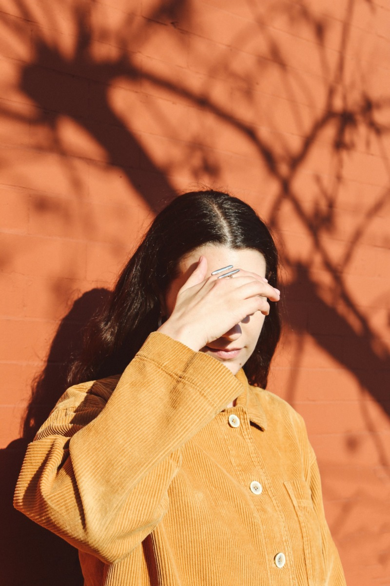 A woman in a tan jacket stands in front of a terracotta wall and shields her eyes from the sun.