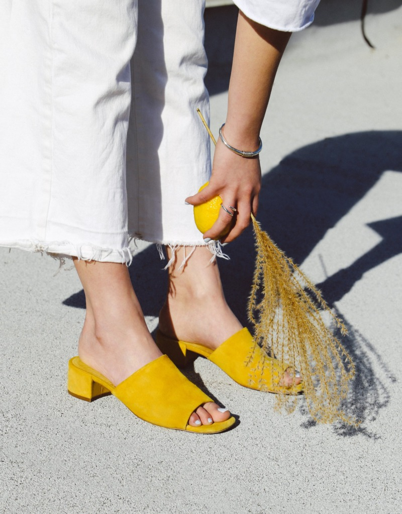 A woman reaches down to the dry, dusty floor, she's holding a lemon and a brush of twigs that match her yellow sandals.