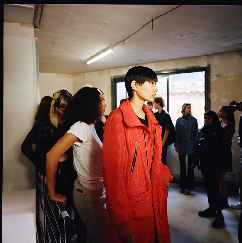 Girls lined up for rehearsal, Asian girl leads the line with a short haircut and a bright red coat