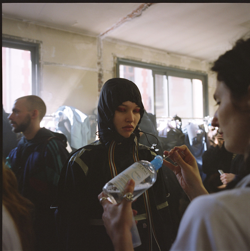 A girl backstage is getting her make-up fixed, hood over head and tight around face with closed eyes wearing fuchsia eyeshadow.
