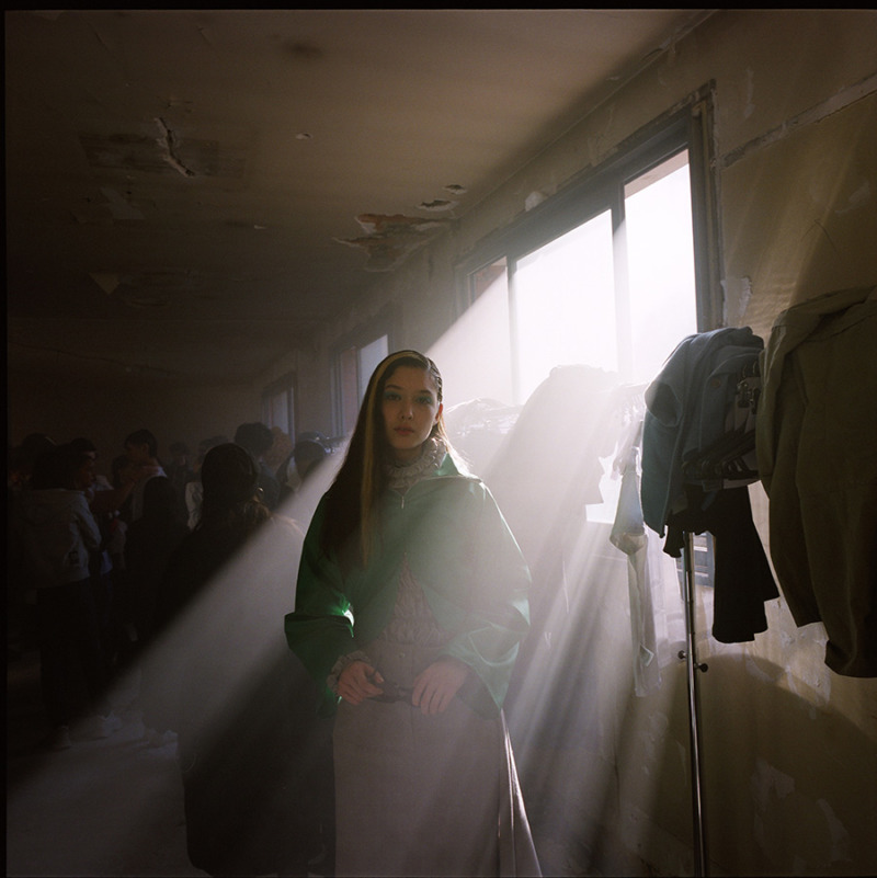 A girl poses backstage in a dark room with sun shining through window, her hair is dark with a single bleached strand and is wearing a green jacket.