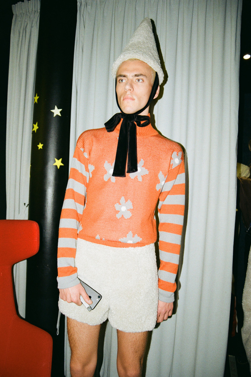 A male stands in front of a white curtain wearing an orange striped and floral top with white shorts and a white cone with black bow secured under his chin.