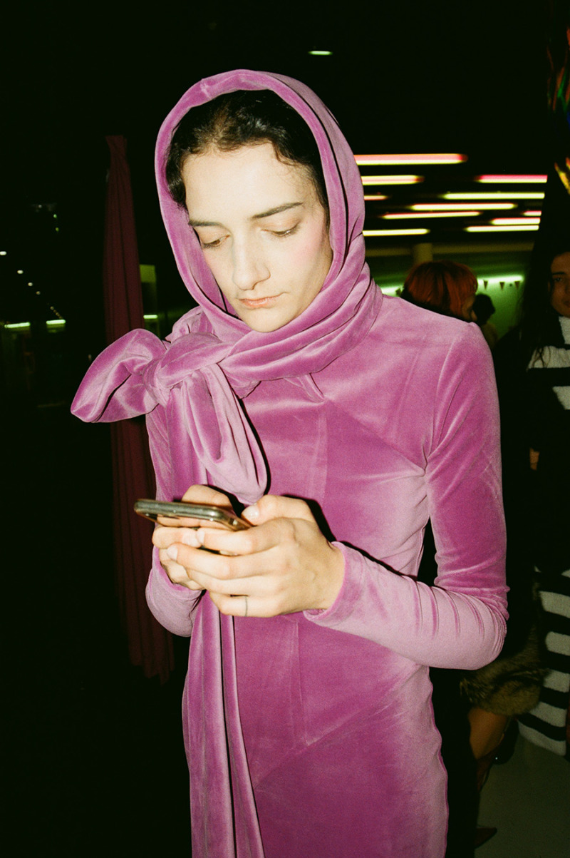 A girl is looking down at her phone wearing a pink velvet, long-sleeved dress and matching headscarf.