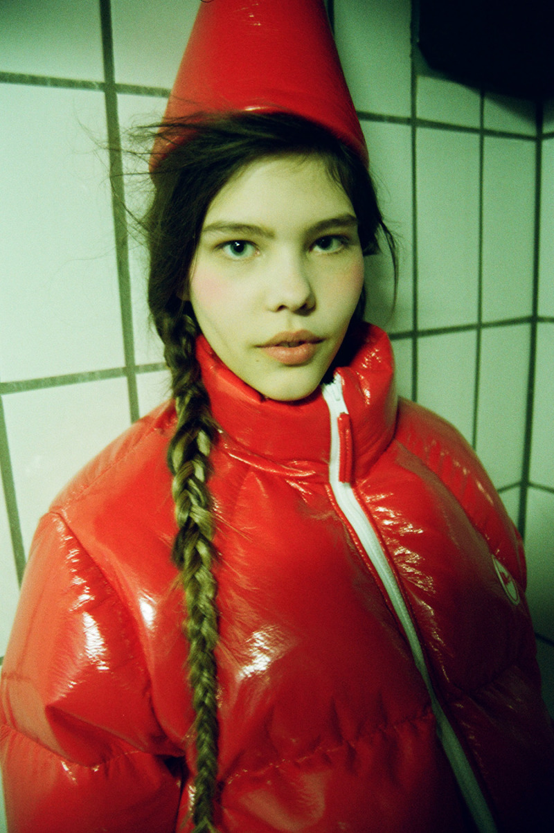 A girl with a single braid to one side poses with a monochromatic background in a red cone hat and a red shiny puffer jacket.