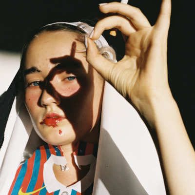 A girl casts a circular shadow ring over her eye. Her bright Barcelona FC t shirt contrasts with a white shawl and the black background.