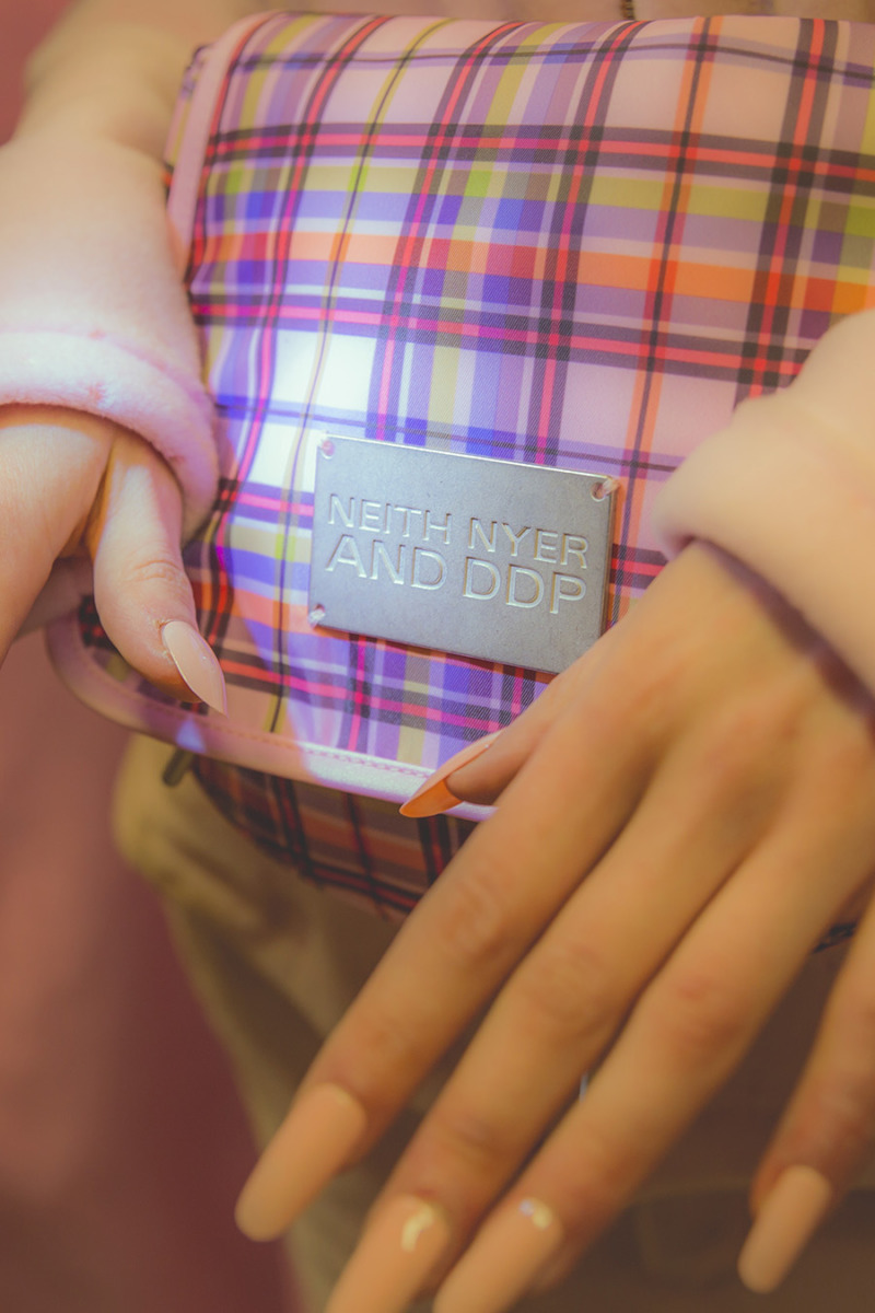 A close up of pink plaid fanny pack, hands with almond shaped pink nails in shot.
