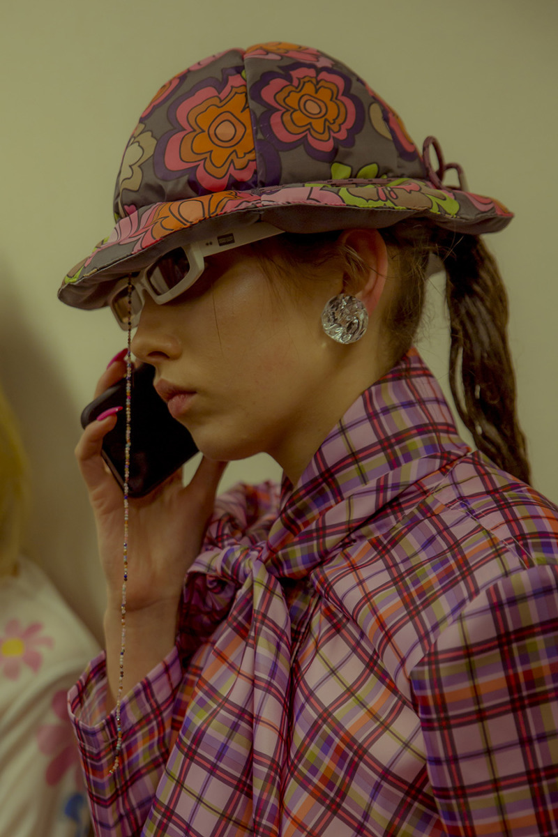 A girl answers her phone wearing a pink plaid pussy-bow top with a floral hat, white sunglasses and large round earrings.