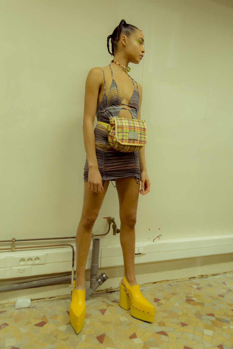 A girl stands in front of a wall looking off-camera. She wears a multi-colour striped bikini-top dress with a yellow plaid fanny-pack and yellow platform ankle boots.