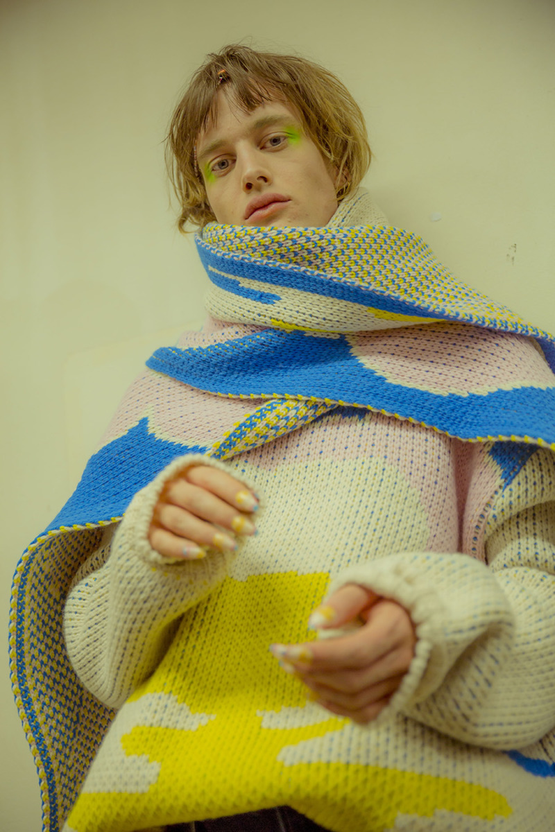 A male with messy blonde hair wears an oversized pink and yellow knit jumper with matching pink and blue scarf. He wears neon green eyeshadow and nail polish that matches his outfit.