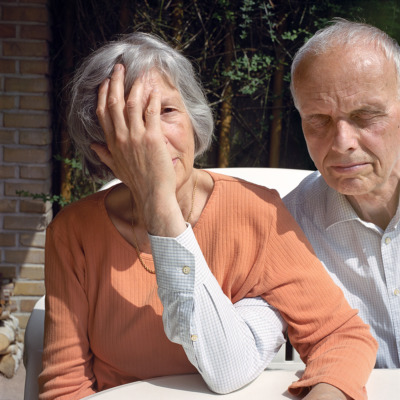 An old man closes his eyes, links arms with his wife, and covers her face.
