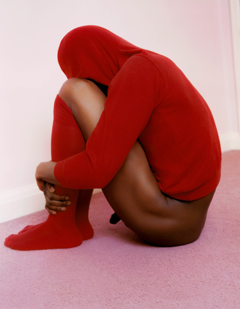 a brown skinned person sitting huddled, wearing only red long socks and a red hooded jumper
