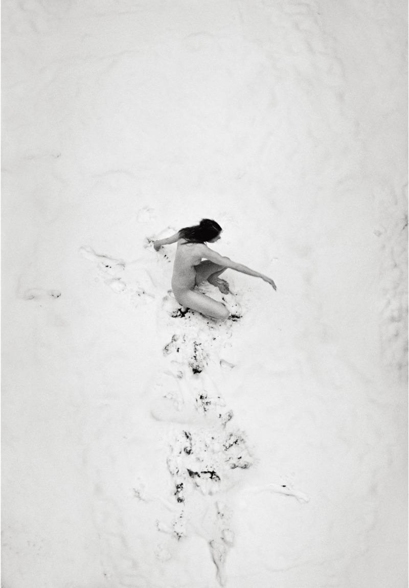 a naked girl slowly descending down a sand dune