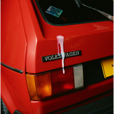 the back left corner of an old volkswagen golf, brightly light and with a white liquid running down the back