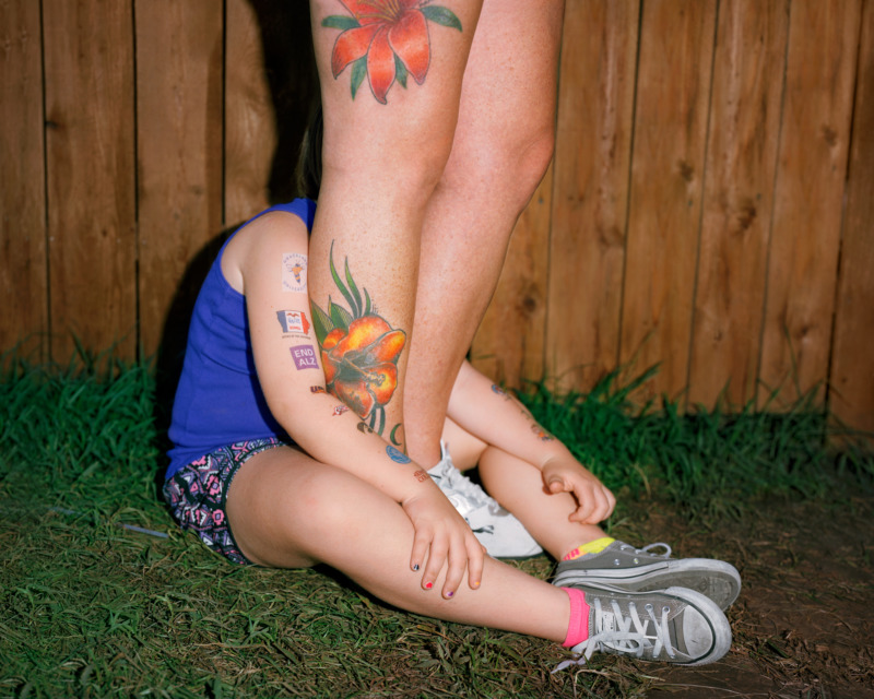 a young person sits on grass, with their face shielded by another person who stands between their legs, tattoos on their calf and thigh