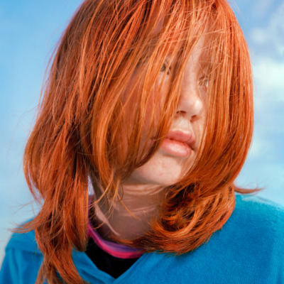 a close up portrait of a girl with bright orange hair covering her face and wearing a blue sweater, looks over her left shoulder