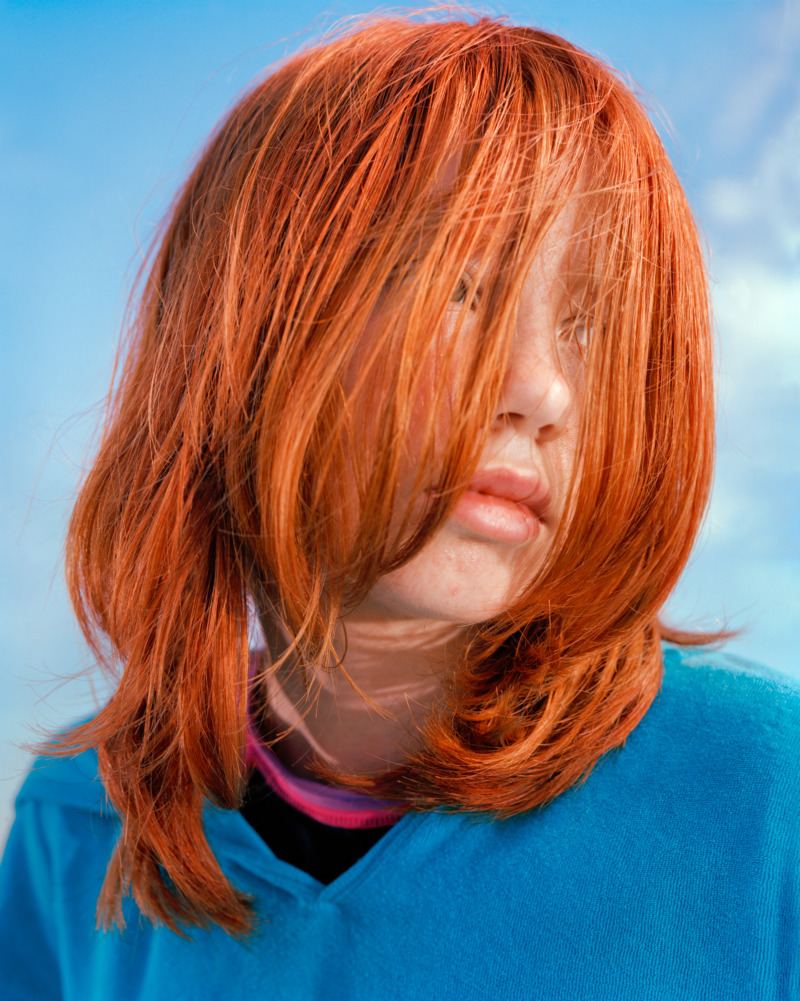 A close up portrait of a girl with bright orange hair covering her face and wearing a blue sweater, looks over her left shoulder.