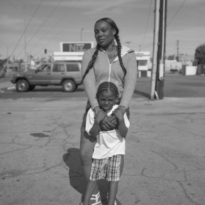 A woman and a young girl stand in an empty car park.