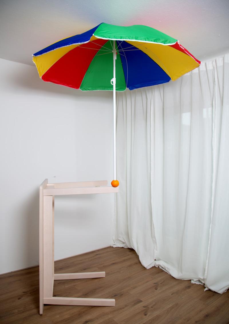 An upturned table balances an orange and a beach umbrella.
