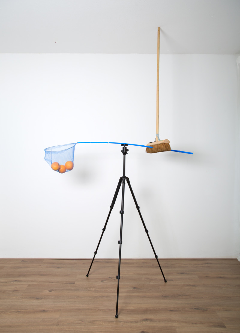 A broom holds a fishing net between the floor and a tripod.