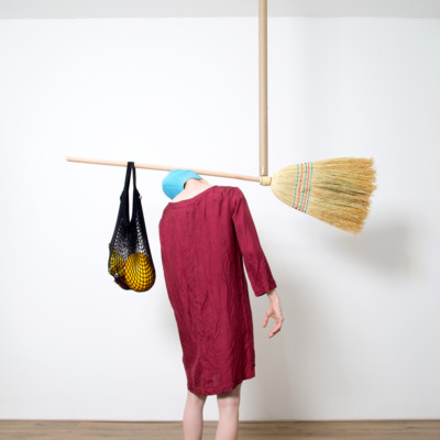 A person carries a broom and a bag of stuff over their shoulders.