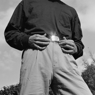 A man rests his hands on his belt, the sun shines from its buckle.