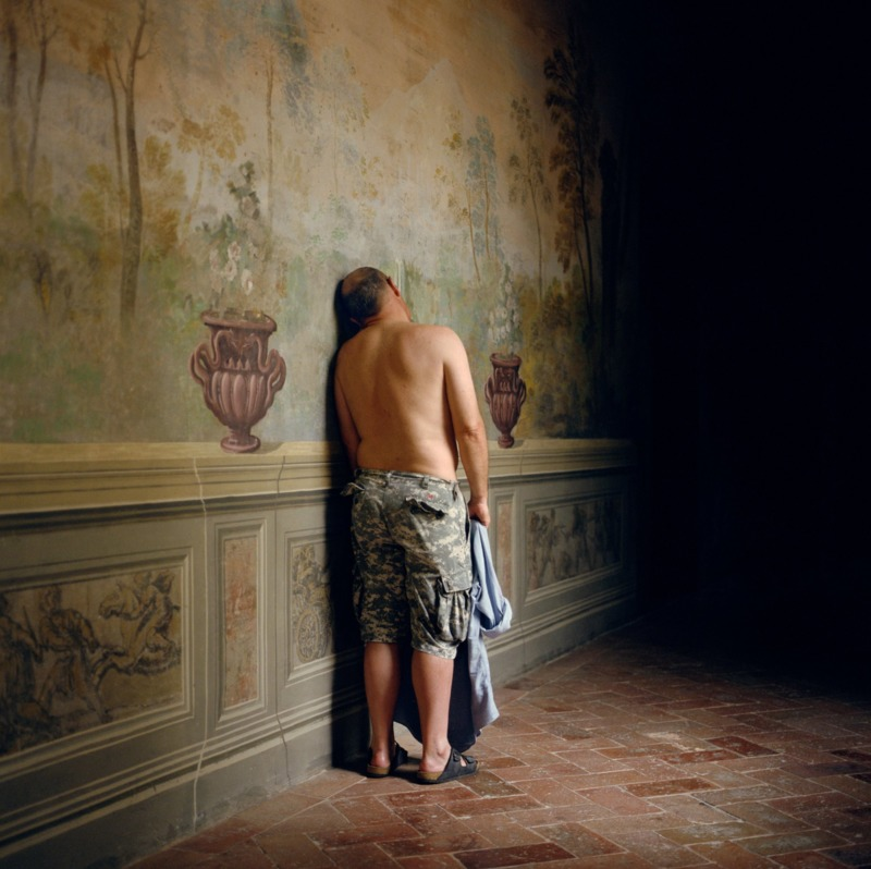 A shirtless man stands lumped against the frescoed wall of an old, rich building.