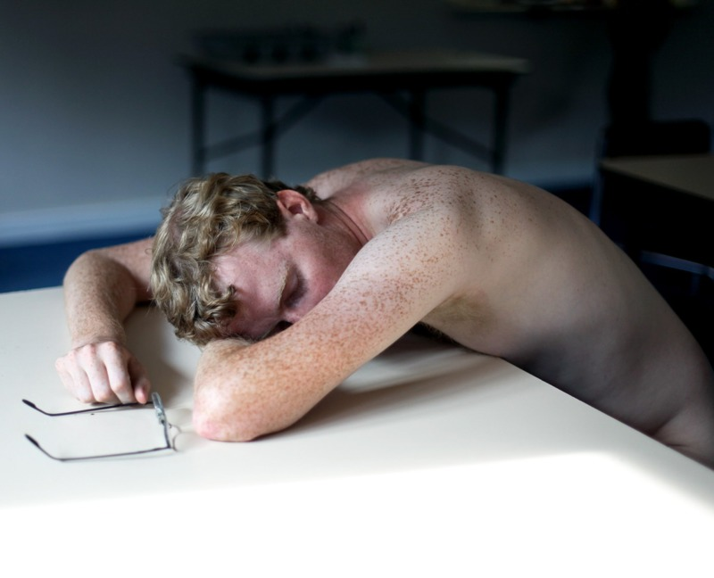 A shirtless young man sleeps on a desk.