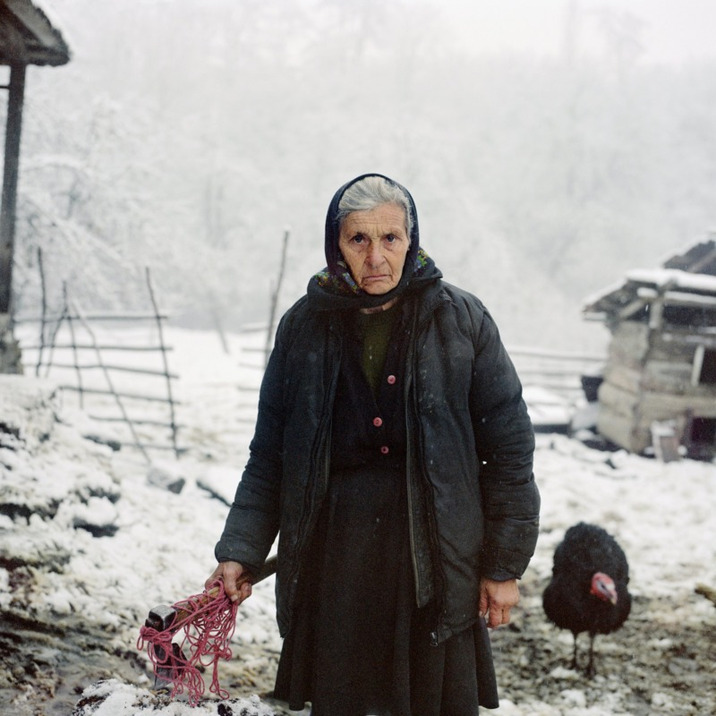 An old babushka stands square to the camera, an axe in her hand.