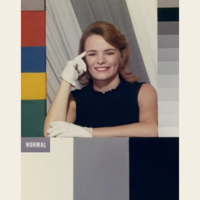 A 'colour girl' card. A test card with a white woman wearing a black dress and white gloves, surrounded by colour reference bars.