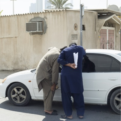 Two men lean into the window of a car, their faces turned away from our view.
