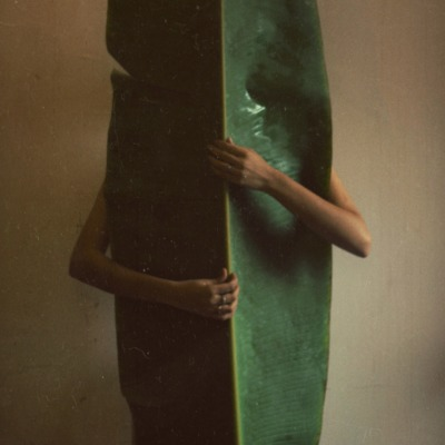 A person holds a large surfboard sized fern leaf that covers the models entire body, leaving only the hands that hug the leaf exposed.