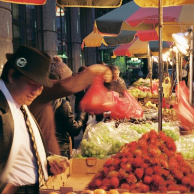 People at a local produce market are shown inspecting and purchasing vendor's goods at dusk.