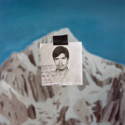An old passport photo has been cut out and pasted on top of an image of a snow-capped mountain.
