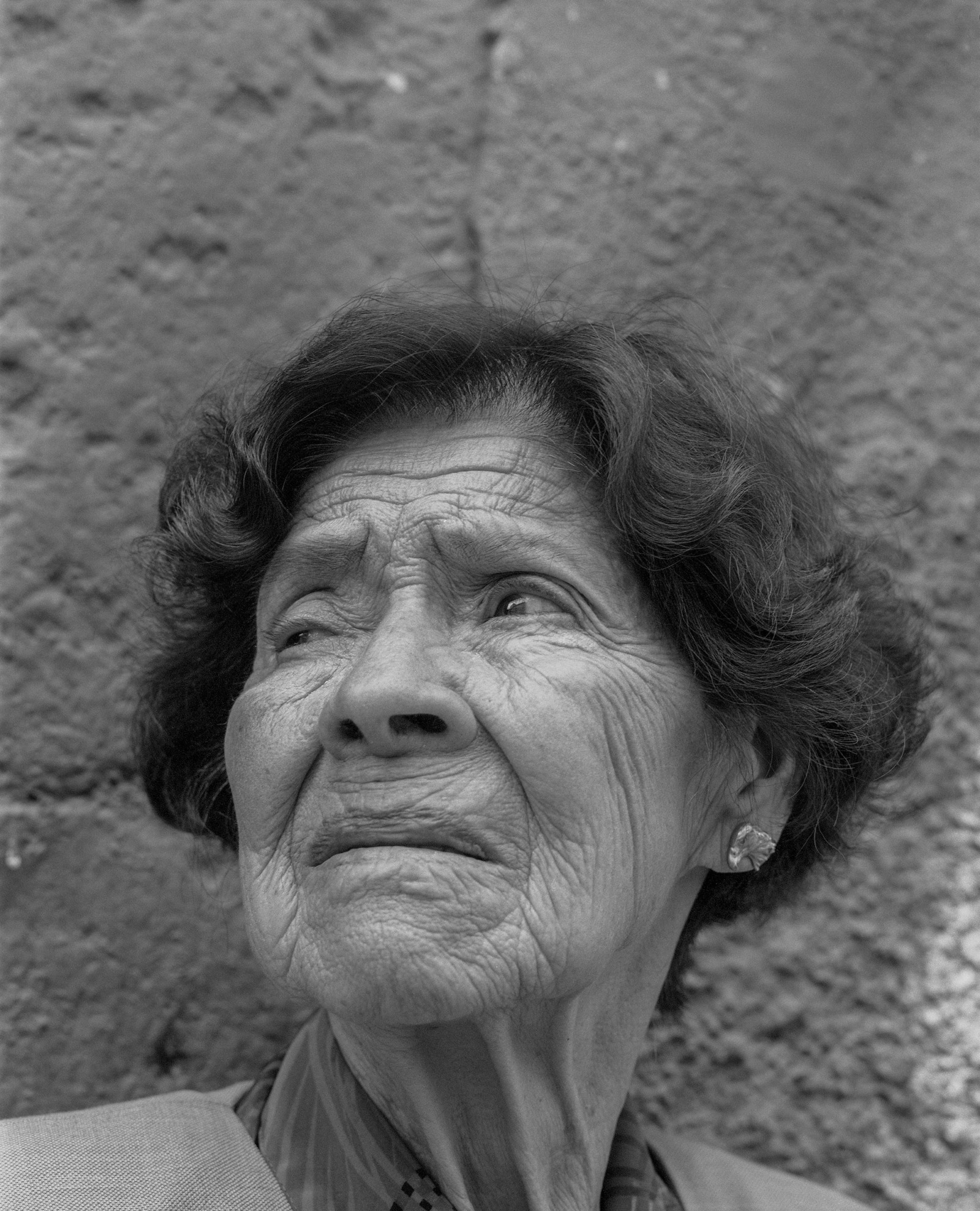 A portrait of an old woman. Her deeply wrinkled skin merges with the concrete behind her.