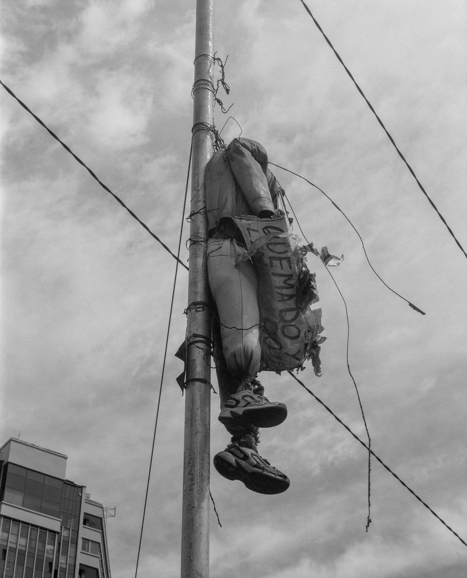 An effigy hangs from a lamppost. A sign around its neck reads 'quema', 'burning'.