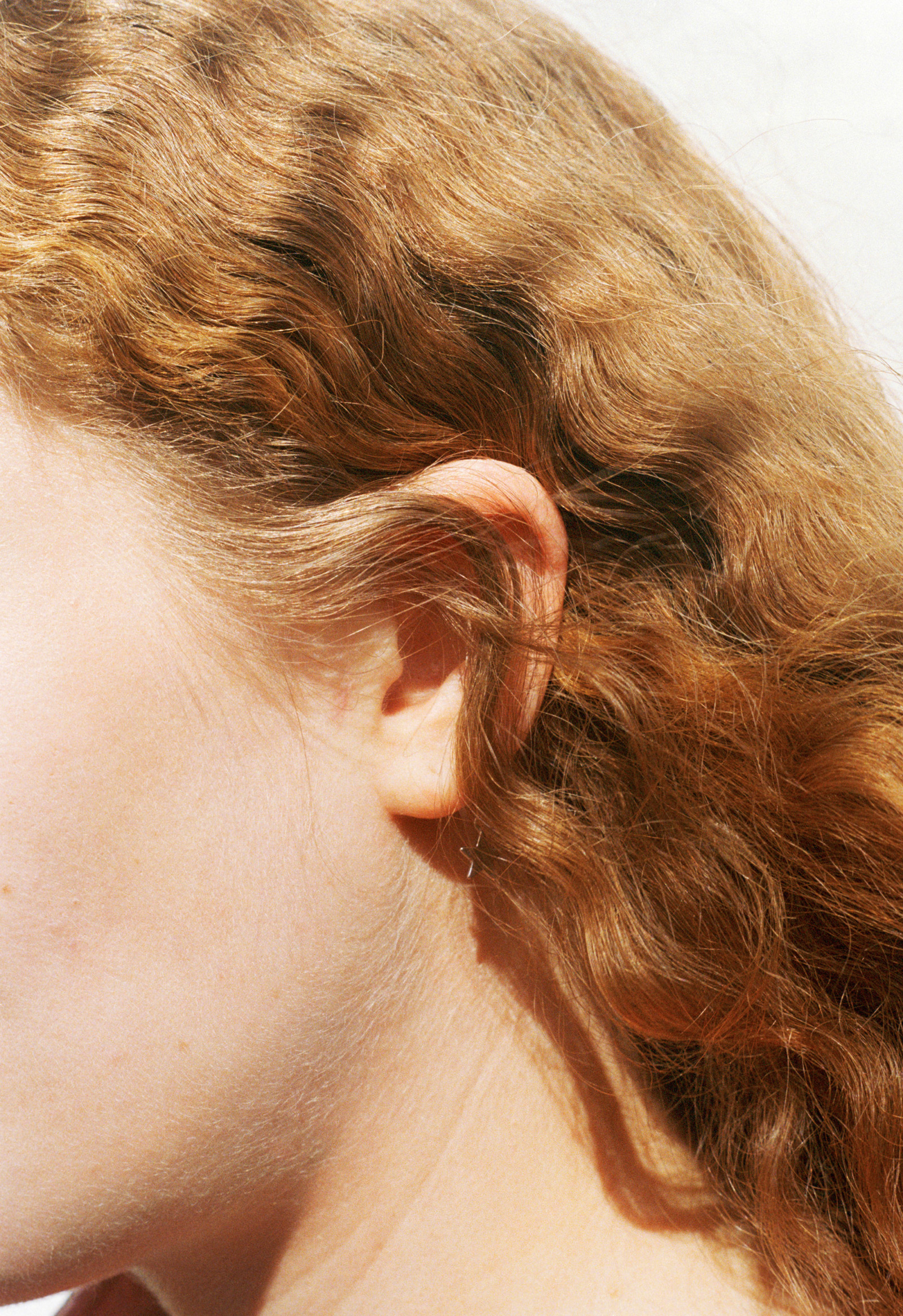 A woman's head in profile with a sweep of curly red hair that covers a gold star earring.