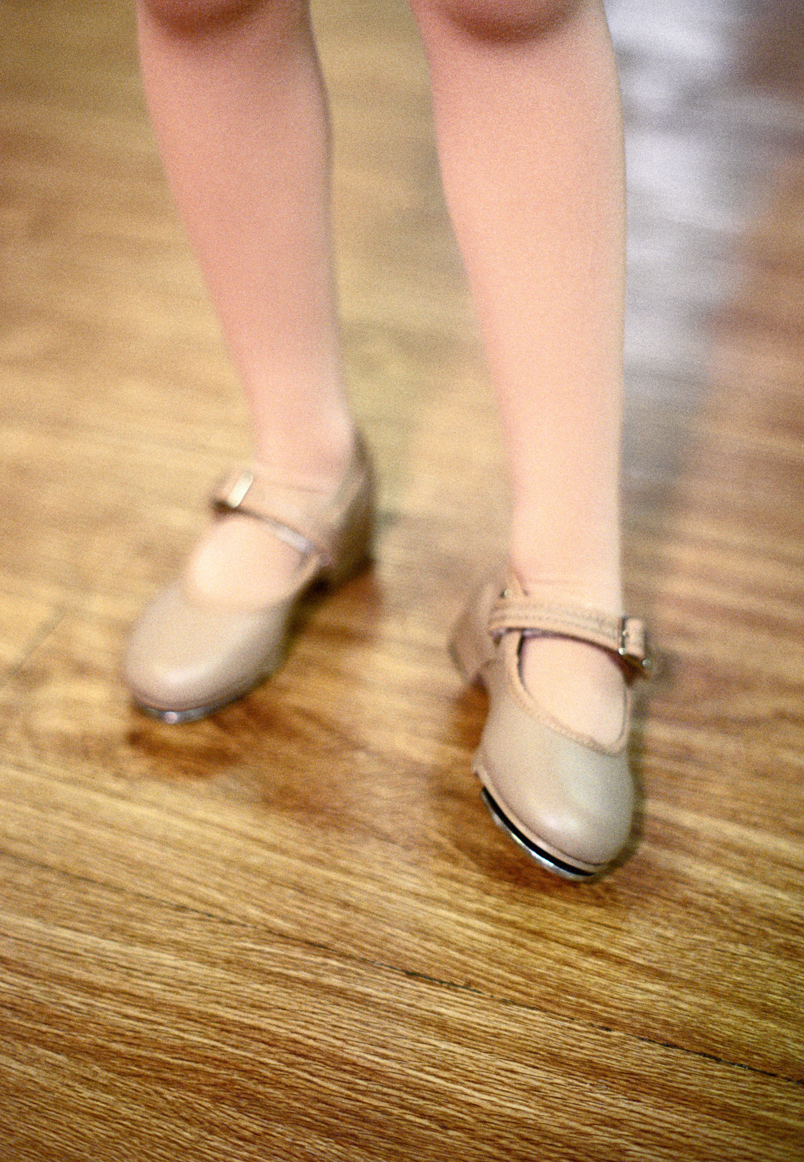 A photograph of a young girl standing anxiously in a tap dance studio.