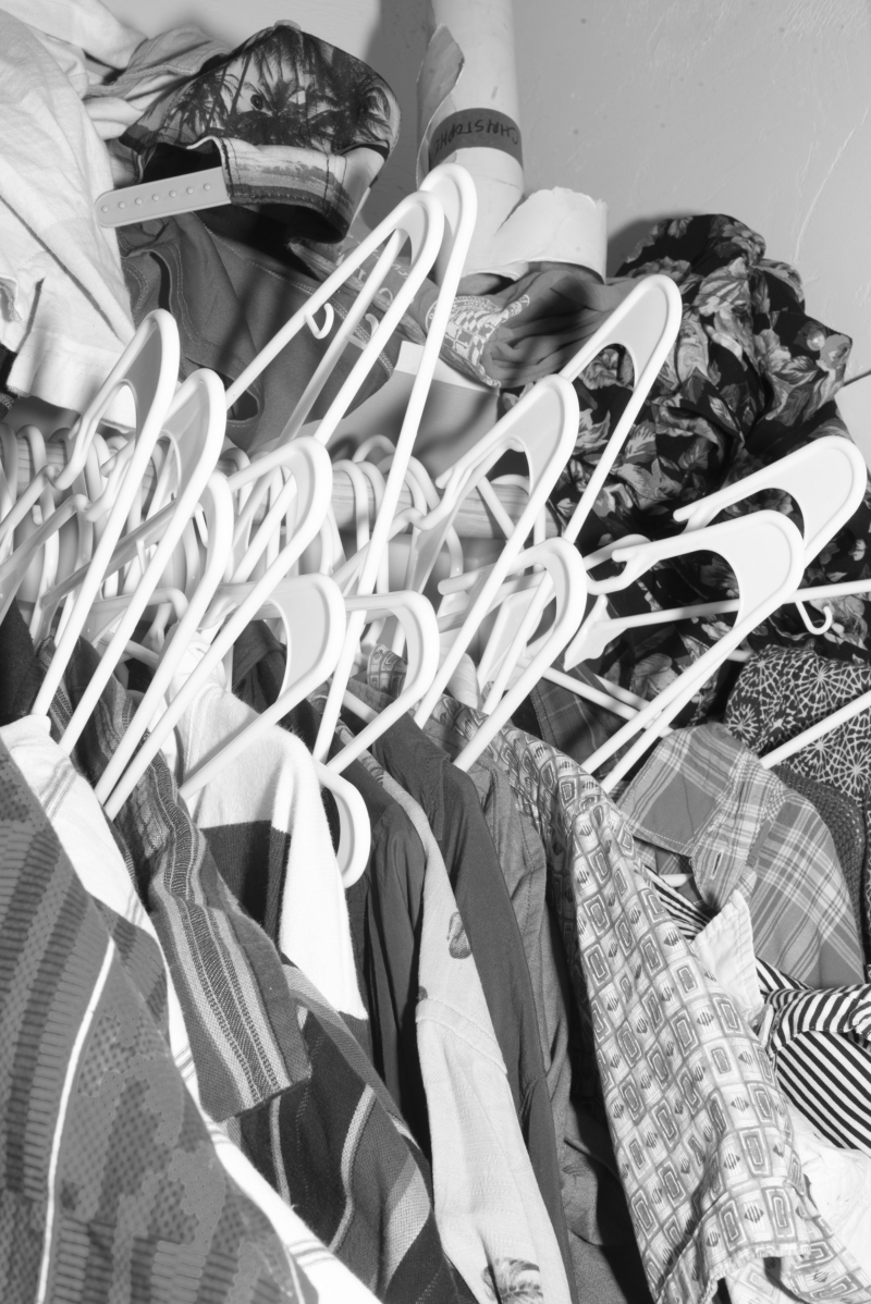 Dozens of assorted shirts hang messily from a clothes rail.