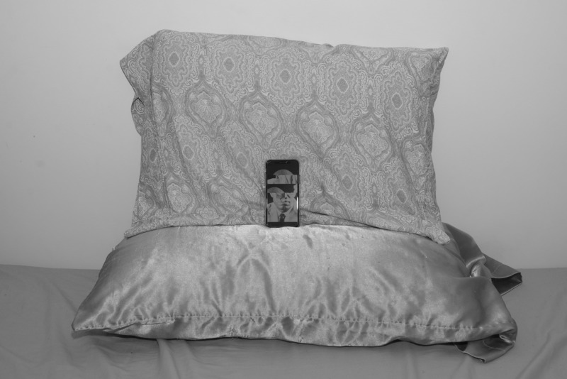 A phone rests on two pillows, it seems to be watching us.