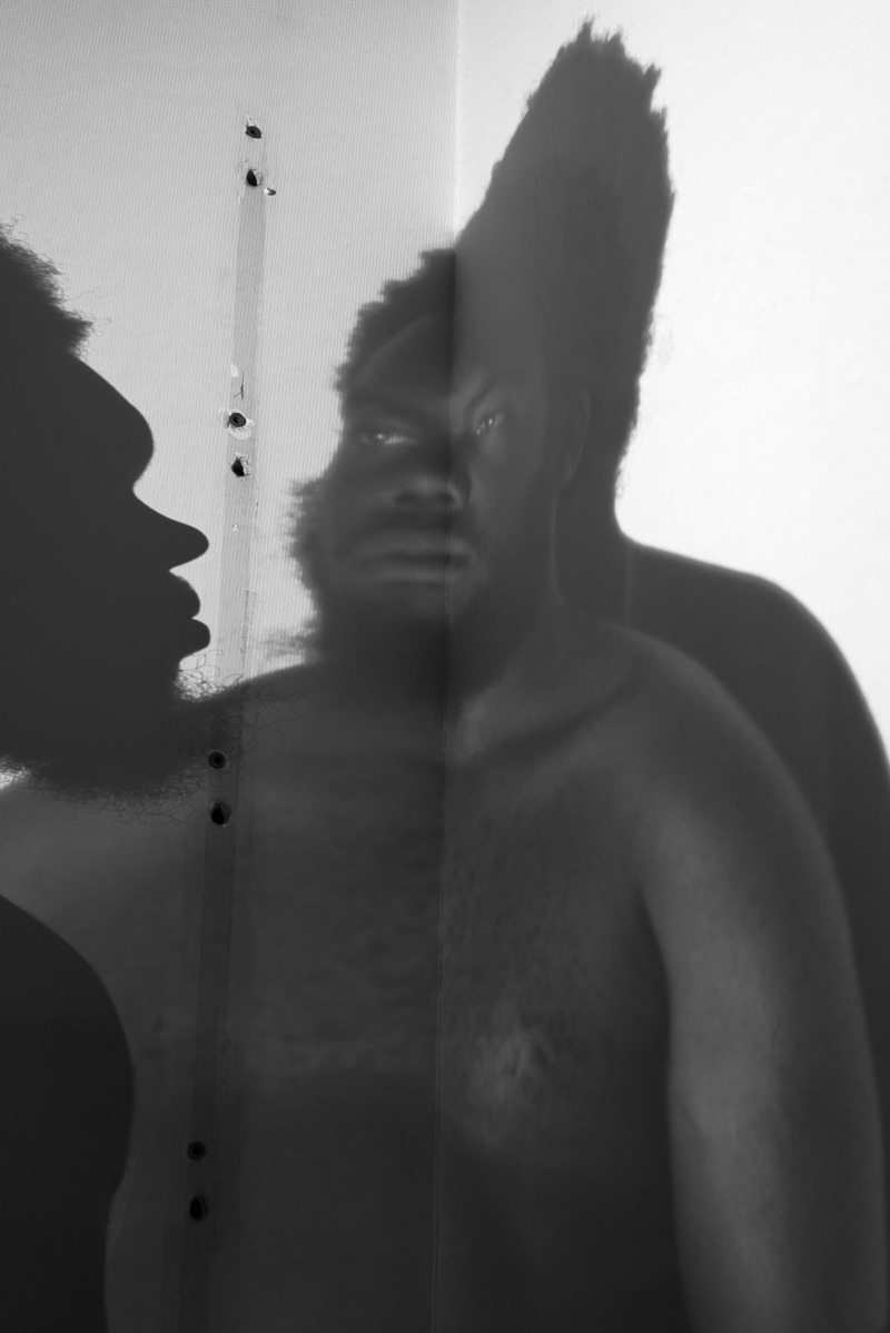 A black, bearded man's distorted reflection is paired with his own shadow.