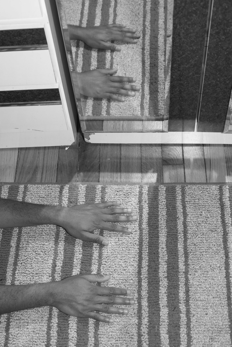 A pair of hands rub a carpet, reflected by a floor length mirror.